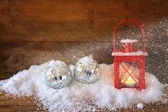 与红色灯笼、中看不中用的物品和雪的圣诞节背景在木背景 闪烁覆盖物 免版税库存图片