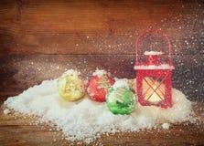 与红色灯笼、中看不中用的物品和雪的圣诞节背景在木背景 闪烁覆盖物 库存图片
