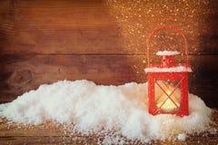 与红色灯笼ans雪的圣诞节背景在与闪烁覆盖物的木背景 免版税库存图片