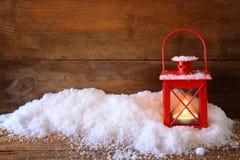 与红色灯笼ans雪的圣诞节背景在木背景 免版税图库摄影