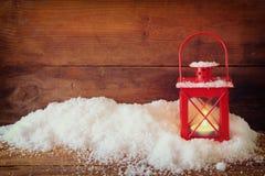 与红色灯笼ans雪的圣诞节背景在木背景 免版税库存图片