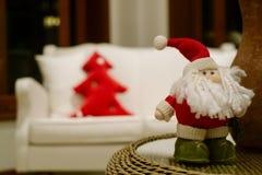 与红色玩具树的圣诞老人小玩具装饰在后面 库存照片