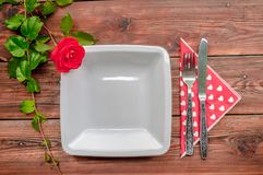 与红色玫瑰和碗筷的木背景 库存照片