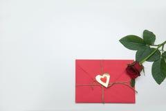 与红色玫瑰的华伦泰卡片在苍白背景 免版税库存照片