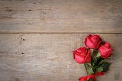 与红色玫瑰的情人节在木的背景和丝带 免版税库存照片