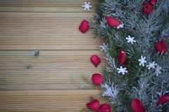 与红色玫瑰花瓣和诗歌选装饰的浪漫圣诞节摄影洒与在木背景的雪与拷贝空间 库存照片