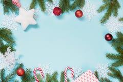 与红色球、雪花和分支的圣诞节创造性的边界在蓝色背景 平的位置 顶视图 复制空间 免版税库存照片
