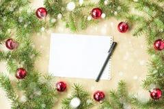 与红色球的欢乐圣诞节边界在冷杉分支和雪花与雪在土气米黄背景 库存图片