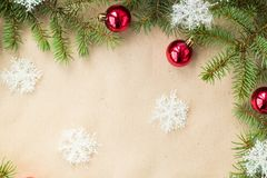 与红色球的欢乐圣诞节边界在冷杉分支和雪花在土气米黄背景 免版税库存图片