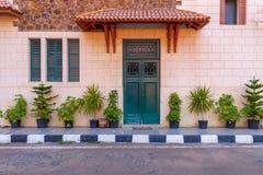 与红色瓦片机盖和上面绿色窗口的绿色木门在石砖墙上关闭 库存照片
