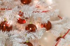 与红色电灯泡和光的美丽的装饰的白色圣诞节快乐树 库存照片