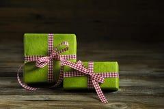 与红色白色方格的丝带的两件绿色礼物在木backgr 图库摄影