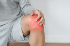与红色的一个人感人的膝盖突出膝盖和关节痛的概念 免版税库存图片