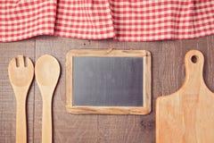 与红色的抽象木背景检查了桌布、黑板和厨房器物 在视图之上 库存照片