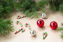 与红色的欢乐圣诞节边界和在冷杉分支和雪花的银球在土气米黄背景 免版税库存图片