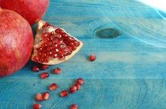 与红色种子的红色水多的果子石榴在木背景 库存图片
