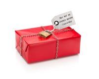 与红色纸的锁着的被包裹的圣诞节礼物与标签 免版税库存照片