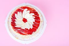 与红色结冰和白色巧克力的自创蛋糕在明亮的色的背景 免版税库存照片