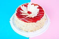 与红色结冰和白色巧克力的自创蛋糕在明亮的色的背景 免版税图库摄影
