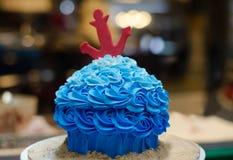 与红色船锚的蓝色buttercream蛋糕在蛋糕商店前面 免版税图库摄影