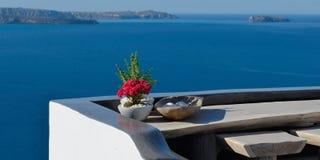 与红色花的全景大阳台在桌上 俯视破火山口在Oia,圣托里尼,希腊 库存图片