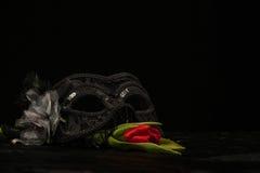 与红色花的化妆舞会面具在黑背景 免版税库存照片