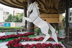 与红色花的抽象白马在门户Ekamai百货商店前面 库存图片