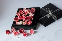 与红色花的蛋白甜饼桃红色在黑匣子 库存照片
