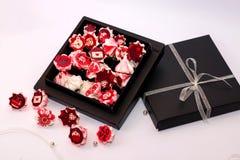 与红色花的蛋白甜饼桃红色在黑匣子 免版税库存图片