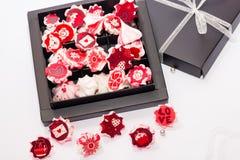 与红色花的蛋白甜饼桃红色在黑匣子 免版税库存照片