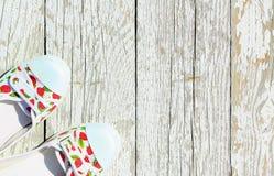 与红色莓果运动鞋的白色在白色木背景 夏天鞋面视图 免版税库存照片