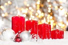 与红色蜡烛和雪的圣诞节背景 库存图片