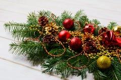 与红色装饰品、金黄小珠和杉木锥体的圣诞节赃物 库存照片