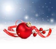 与红色装饰品和圣诞快乐丝带的假日背景在雪 免版税库存图片