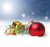 与红色装饰品和降雪的圣诞节背景 免版税库存照片