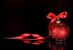 与红色装饰品的圣诞节在黑背景的背景和丝带 免版税库存图片