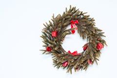 与红色装饰品的圣诞节花圈在墙壁上 免版税库存图片