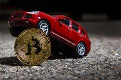 与红色豪华天桥汽车模型的Bitcoin物理金黄硬币特写镜头  黑暗的主题 库存图片