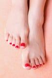 与红色趾甲的妇女英尺在毛巾 库存照片