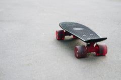 与红色轮子的黑塑料滑板在沥青 免版税库存图片