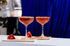 与红色酒精鸡尾酒的两块马蒂尼鸡尾酒玻璃在木bo 免版税库存图片
