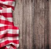 与红色野餐桌布的老木桌 免版税库存照片