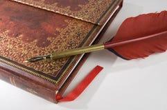 与红色钢笔的古色古香的红色书 免版税库存照片