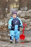 与红色铁锹的小男孩立场在水池 库存图片