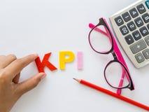 与红色铅笔和桃红色玻璃的KPI字母表 免版税库存照片