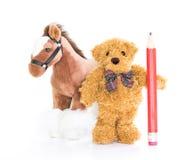 与红色铅笔和马的玩具熊 免版税图库摄影