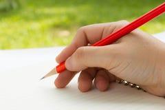 与红色铅笔的右手文字 库存照片