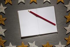 与红色铅笔的笔记薄在板岩背景,圣诞节框架 库存照片