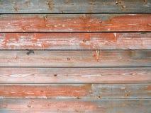 与红色雪片油漆的被风化的老木纹理 免版税图库摄影