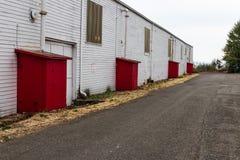 与红色露出的被放弃的老仓库大厦 库存图片